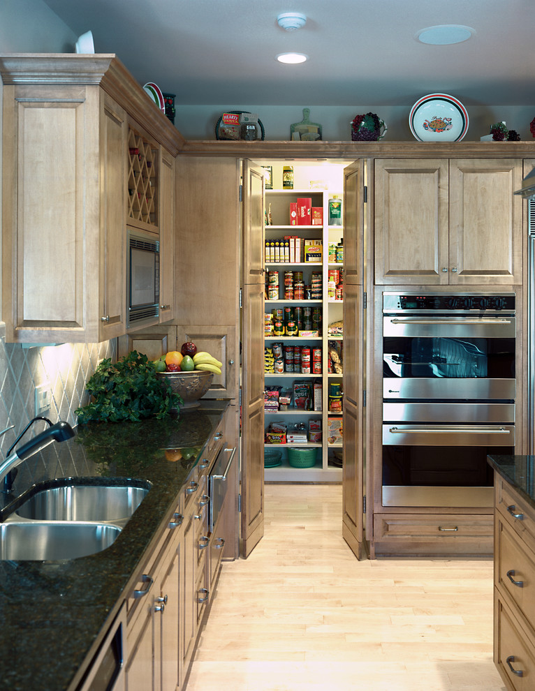 Example of a classic light wood floor kitchen design in Omaha with an undermount sink, recessed-panel cabinets, medium tone wood cabinets, gray backsplash and stainless steel appliances