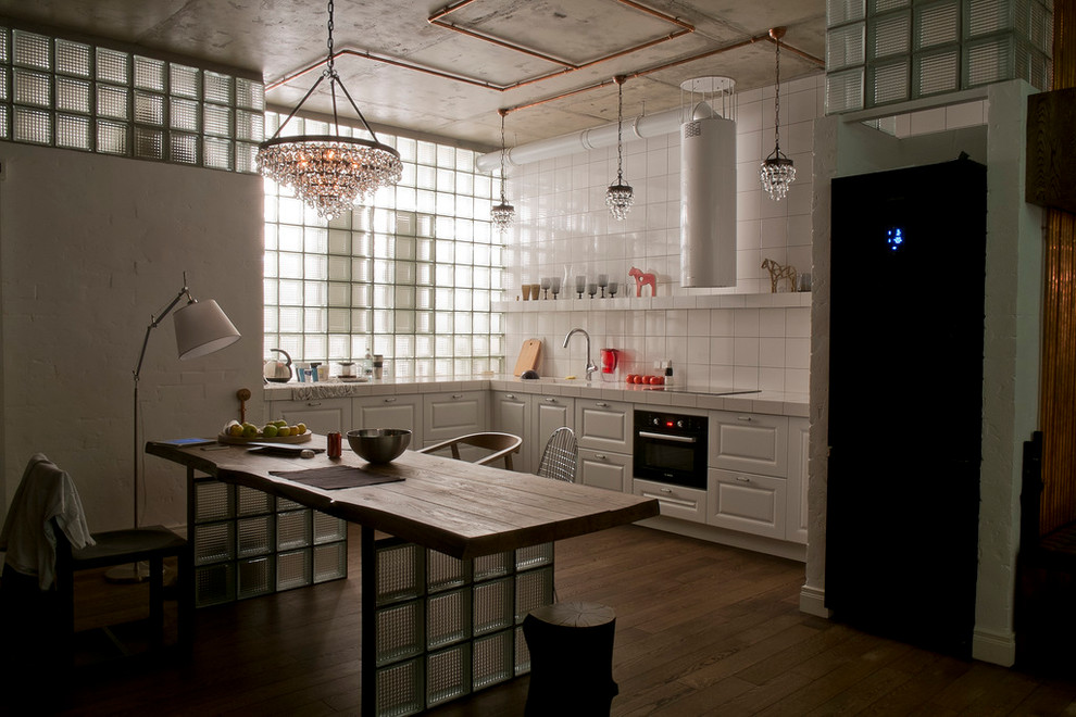 Example of an urban dark wood floor open concept kitchen design in Moscow with white cabinets, tile countertops, white backsplash and black appliances