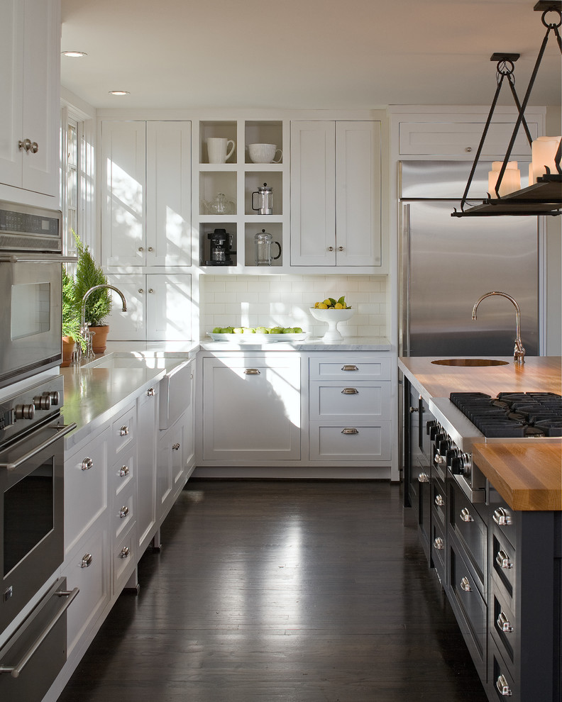 Enclosed kitchen - large cottage l-shaped dark wood floor and brown floor enclosed kitchen idea in San Diego with shaker cabinets, an island, a farmhouse sink, white cabinets, wood countertops, white backsplash, subway tile backsplash and stainless steel appliances