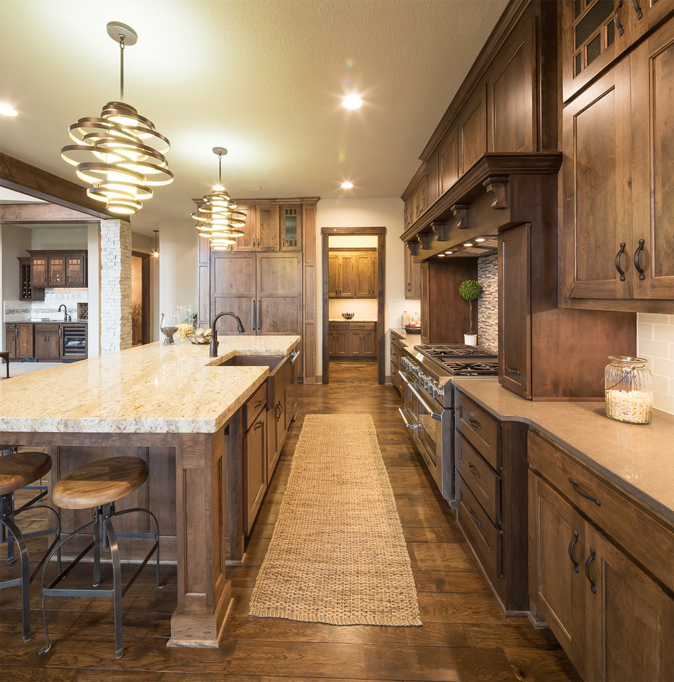 Mountain style dark wood floor kitchen photo in Dallas with a farmhouse sink, shaker cabinets, dark wood cabinets, beige backsplash, subway tile backsplash and an island