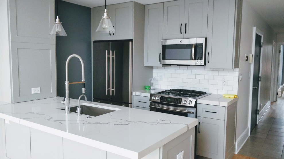 Small minimalist galley light wood floor and brown floor eat-in kitchen photo in New York with an undermount sink, shaker cabinets, gray cabinets, quartz countertops, stainless steel appliances, white backsplash, subway tile backsplash, an island and white countertops