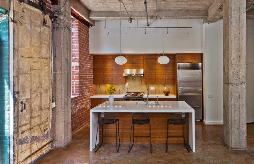 Example of an urban galley kitchen design in San Francisco with an integrated sink, stainless steel appliances, flat-panel cabinets, medium tone wood cabinets and quartz countertops