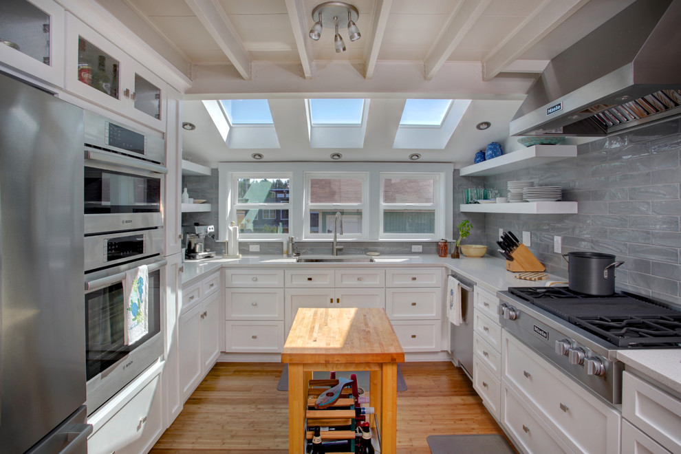 Example of a transitional u-shaped medium tone wood floor and brown floor kitchen design in Seattle with an undermount sink, shaker cabinets, white cabinets, gray backsplash, stainless steel appliances and an island