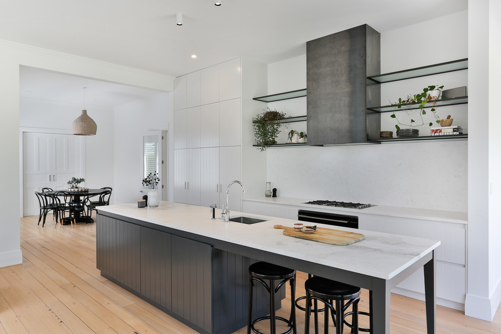 Inspiration for a mid-sized transitional galley light wood floor and brown floor open concept kitchen remodel in Auckland with white cabinets, marble countertops, white backsplash, marble backsplash, black appliances, an island, white countertops, an undermount sink and flat-panel cabinets