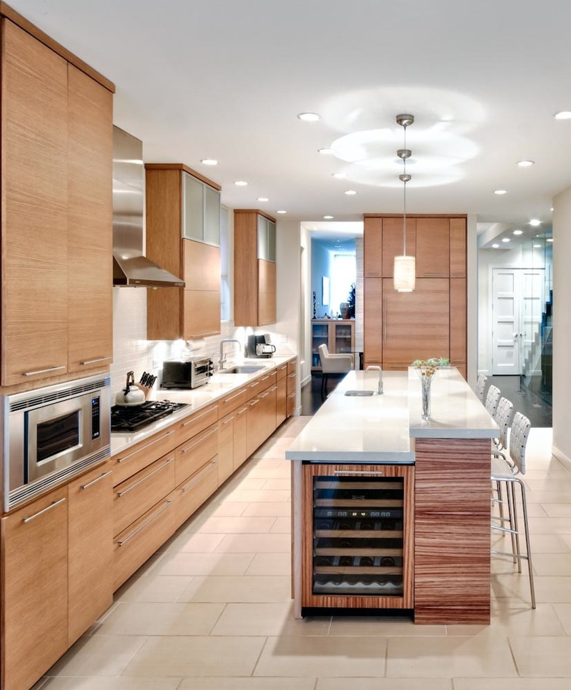 Inspiration for a large contemporary galley ceramic floor eat-in kitchen remodel in Chicago with flat-panel cabinets, light wood cabinets, white backsplash, subway tile backsplash, paneled appliances, an island, an undermount sink and solid surface countertops