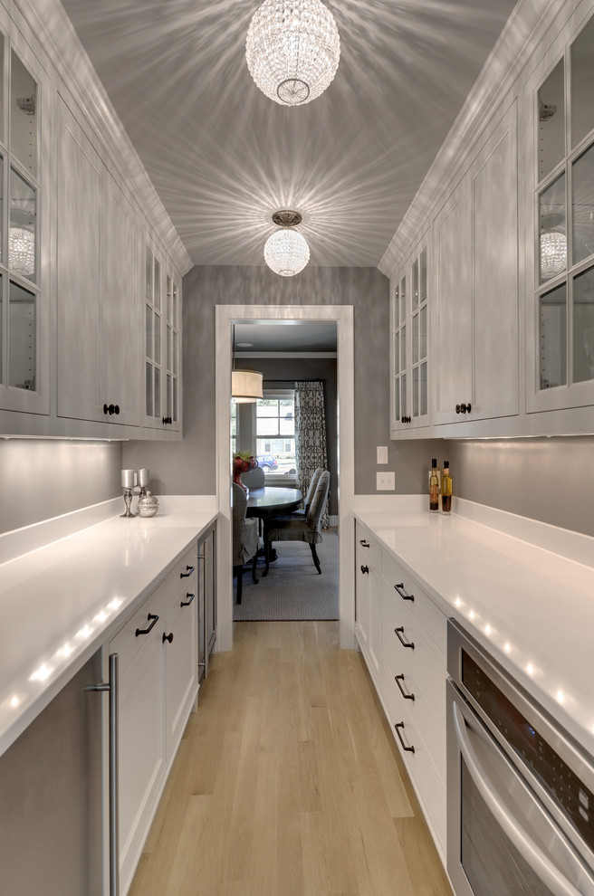 Enclosed kitchen - traditional galley enclosed kitchen idea in Minneapolis with glass-front cabinets, white cabinets and stainless steel appliances