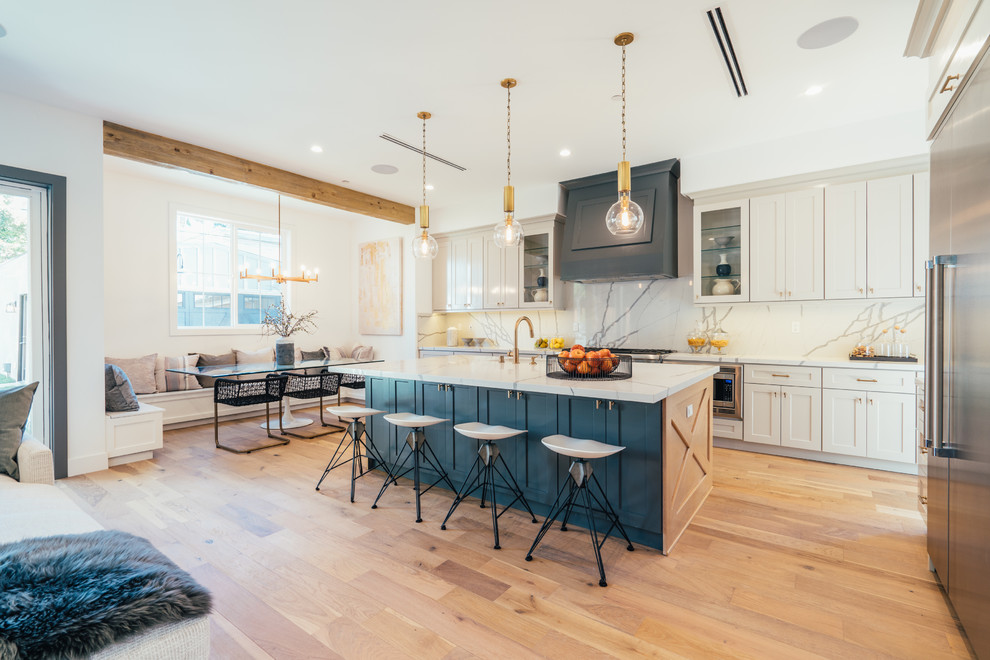 Inspiration for a coastal light wood floor and beige floor open concept kitchen remodel in Los Angeles with shaker cabinets, white cabinets, white backsplash, stone slab backsplash, stainless steel appliances, an island and white countertops