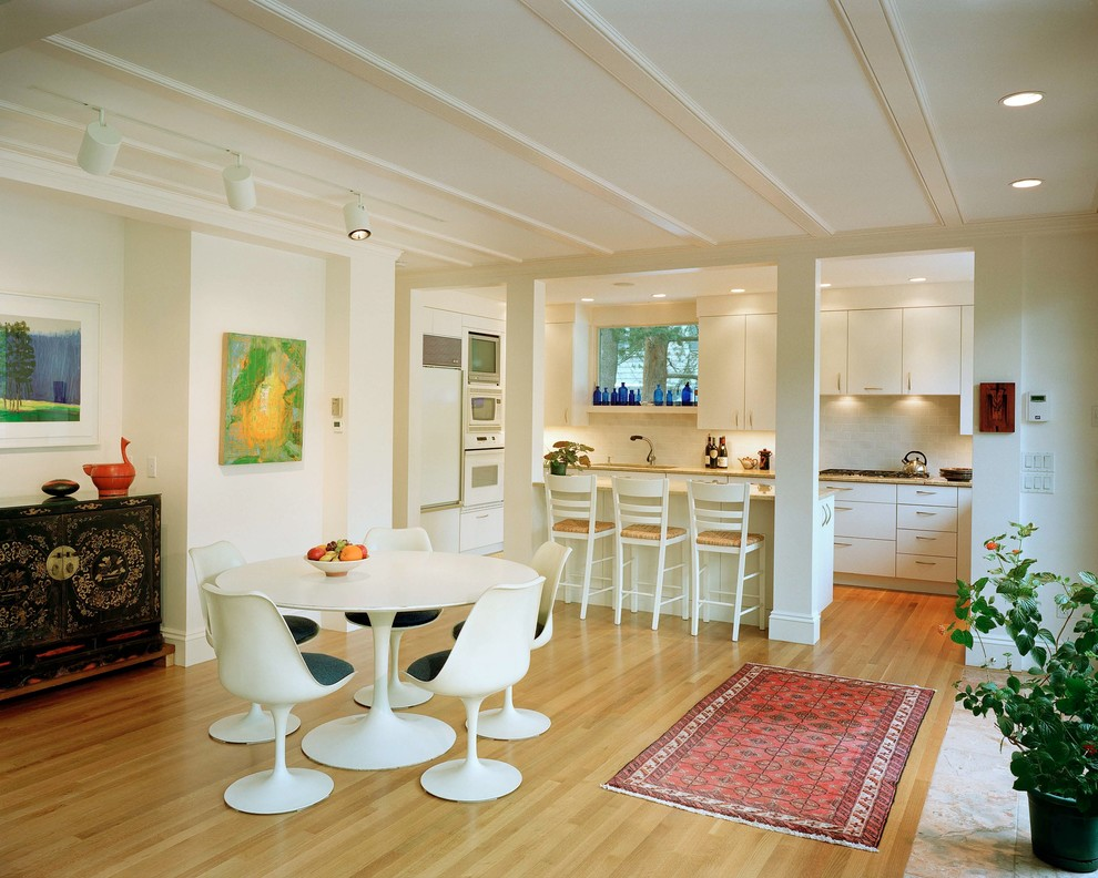 Eat-in kitchen - small contemporary galley light wood floor and beige floor eat-in kitchen idea in Boston with flat-panel cabinets, white cabinets, white appliances, granite countertops, white backsplash, a peninsula and beige countertops