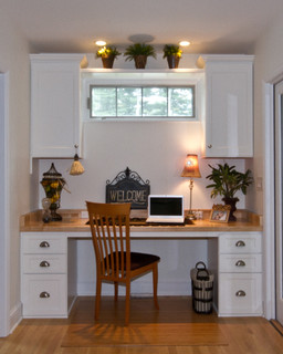 Small home office built at one end of narrow space.