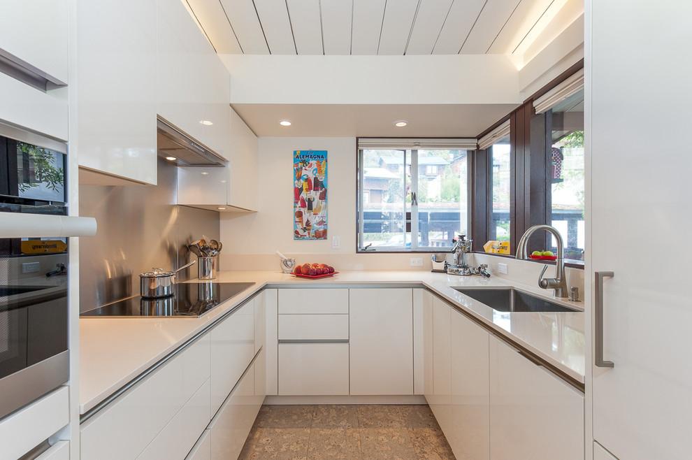 Enclosed kitchen - small contemporary u-shaped enclosed kitchen idea in San Francisco with an undermount sink, flat-panel cabinets, white cabinets, metallic backsplash, metal backsplash, paneled appliances, no island and quartz countertops