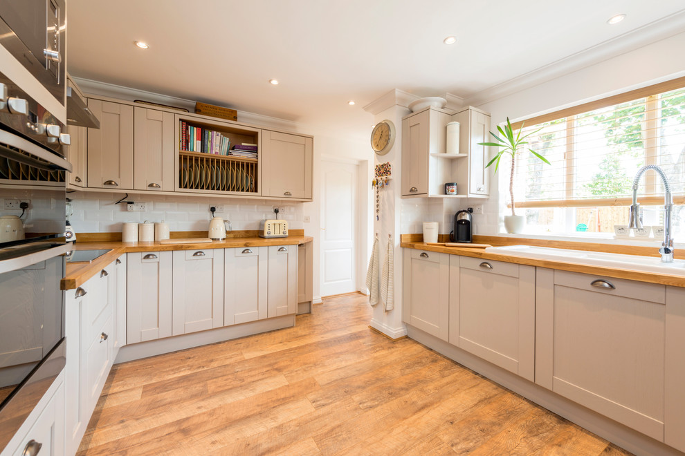 Inspiration for a mid-sized country laminate floor and brown floor enclosed kitchen remodel in Dorset with a double-bowl sink, shaker cabinets, beige cabinets, wood countertops, stainless steel appliances, white backsplash and subway tile backsplash