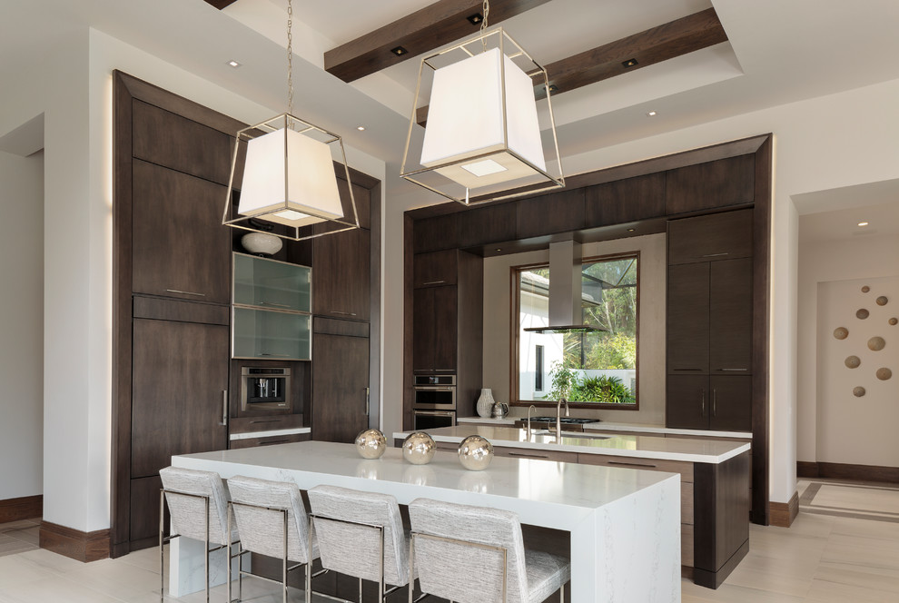 Example of a large minimalist l-shaped porcelain tile and beige floor kitchen design in Miami with flat-panel cabinets, dark wood cabinets, paneled appliances, two islands, white countertops and an undermount sink