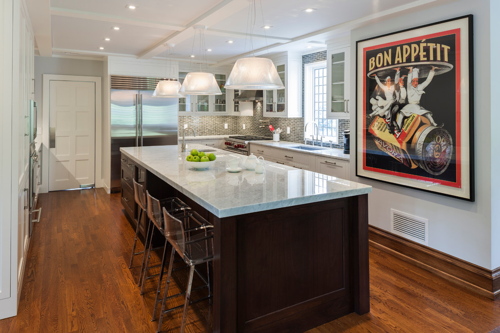 Kitchen - transitional l-shaped kitchen idea in New York with an undermount sink, glass-front cabinets, white cabinets, gray backsplash and stainless steel appliances