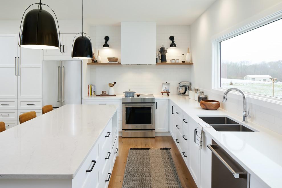 Idee per una cucina country con ante bianche, top in laminato, elettrodomestici in acciaio inossidabile, parquet chiaro e top bianco