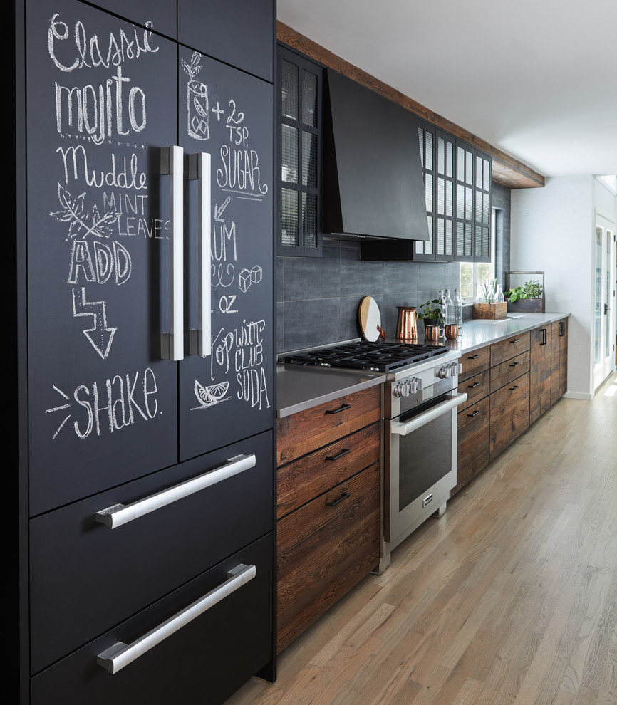 Eat-in kitchen - large industrial galley light wood floor and beige floor eat-in kitchen idea in New York with an undermount sink, flat-panel cabinets, dark wood cabinets, gray backsplash, black appliances, an island and gray countertops