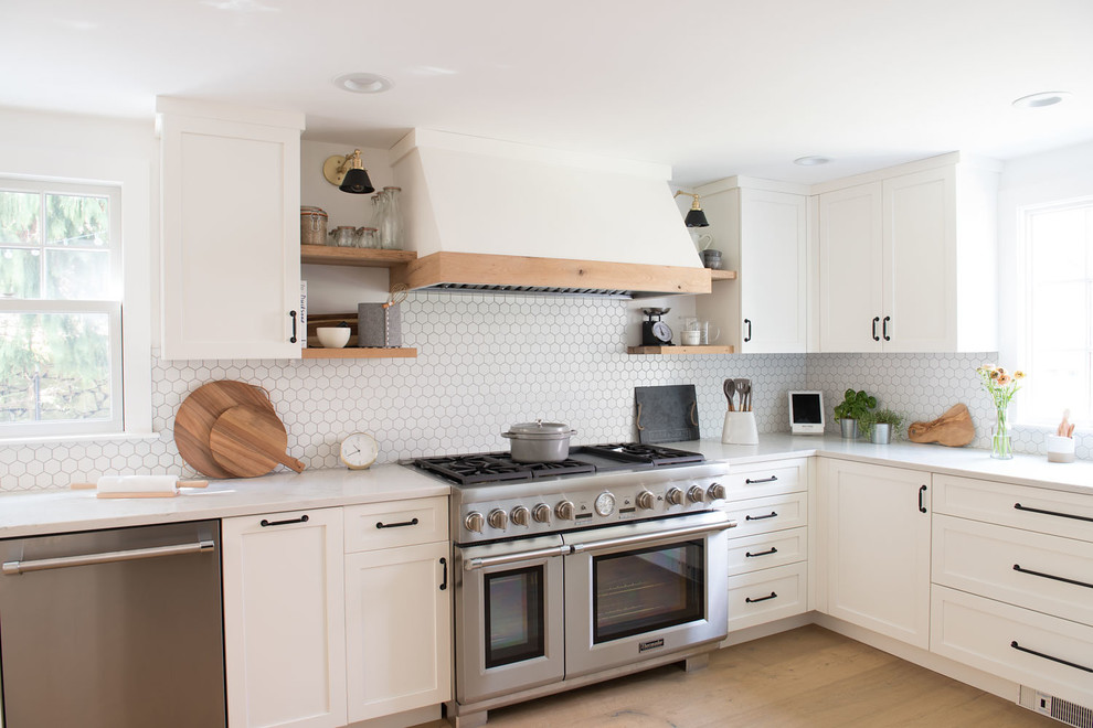 Large cottage l-shaped light wood floor and beige floor kitchen photo in Boston with shaker cabinets, white cabinets, quartz countertops, white backsplash, stainless steel appliances and white countertops