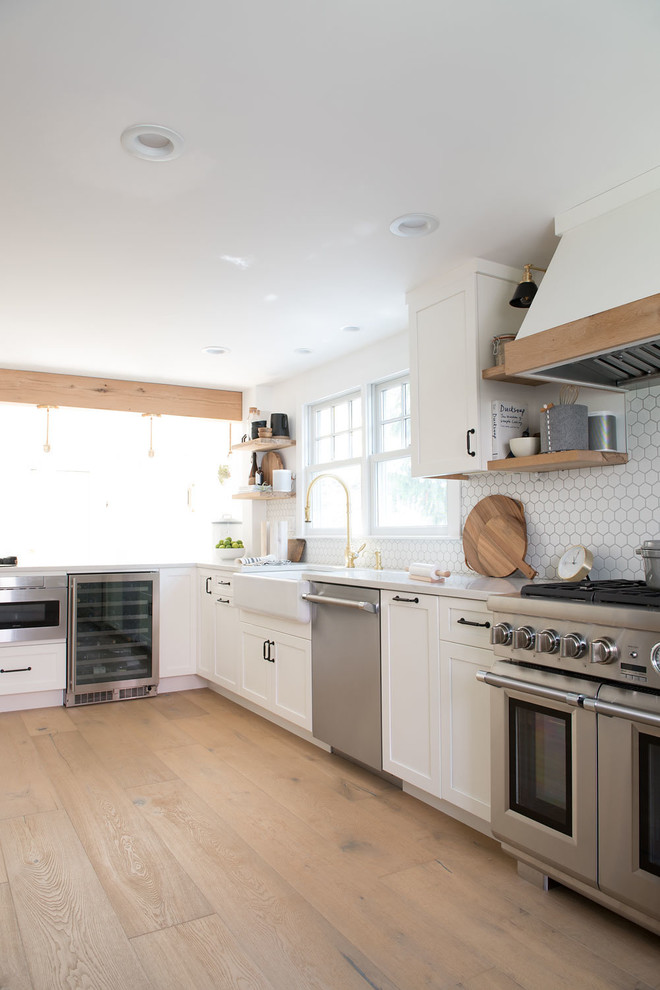 Eat-in kitchen - large country u-shaped light wood floor and brown floor eat-in kitchen idea in Boston with shaker cabinets, white cabinets, quartz countertops, white backsplash, mosaic tile backsplash, stainless steel appliances, a peninsula and white countertops