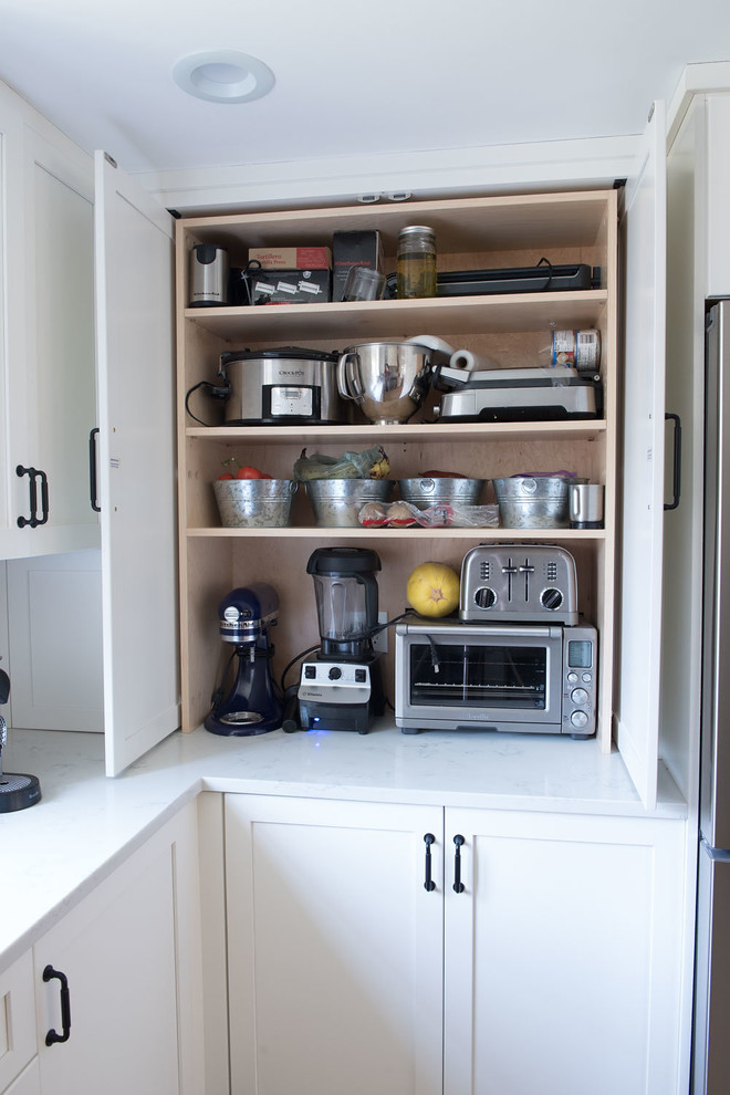 Large cottage u-shaped light wood floor and brown floor eat-in kitchen photo in Boston with shaker cabinets, white cabinets, quartz countertops, white backsplash, mosaic tile backsplash, stainless steel appliances, a peninsula and white countertops