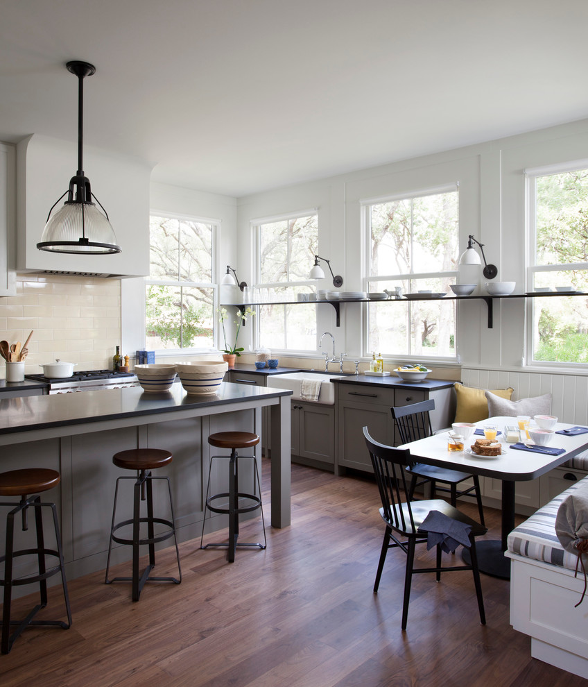 Country eat-in kitchen photo in Austin with a farmhouse sink, recessed-panel cabinets, gray cabinets, beige backsplash, subway tile backsplash and stainless steel appliances