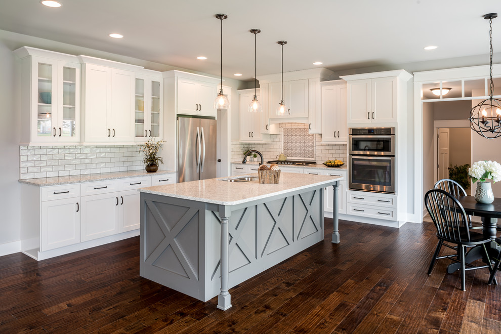 Design ideas for a country l-shaped eat-in kitchen in Philadelphia with a double-bowl sink, shaker cabinets, white cabinets, white splashback, subway tile splashback, stainless steel appliances, dark hardwood floors, with island and brown floor.