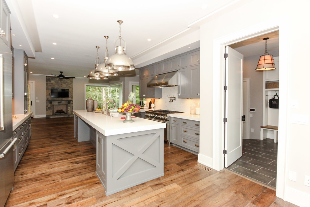 Mid-sized cottage u-shaped medium tone wood floor enclosed kitchen photo in Raleigh with a farmhouse sink, shaker cabinets, gray cabinets, solid surface countertops, white backsplash, stainless steel appliances and an island