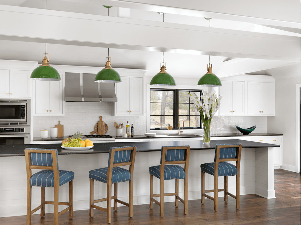 Inspiration for a transitional brown floor and dark wood floor kitchen remodel in St Louis with shaker cabinets, white cabinets, soapstone countertops, white backsplash, an island and stainless steel appliances