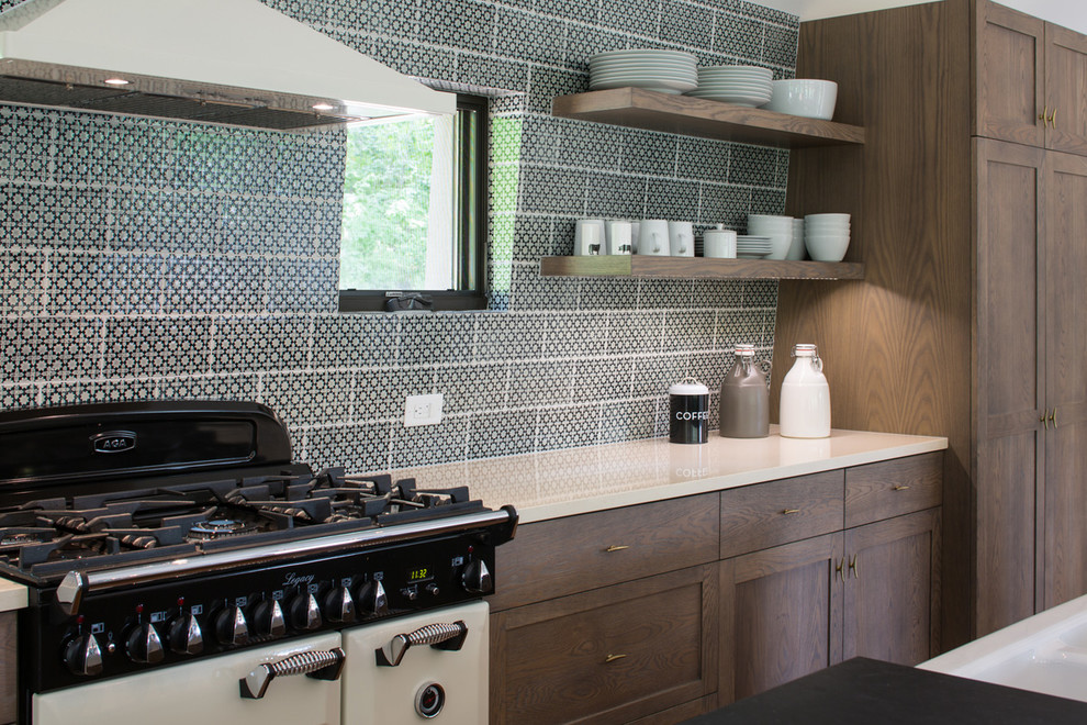 Inspiration for a large rustic single-wall medium tone wood floor eat-in kitchen remodel in Other with a farmhouse sink, shaker cabinets, medium tone wood cabinets, solid surface countertops, multicolored backsplash, ceramic backsplash, stainless steel appliances and an island