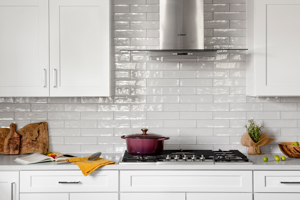Inspiration for a large farmhouse u-shaped dark wood floor and brown floor eat-in kitchen remodel in DC Metro with a farmhouse sink, recessed-panel cabinets, white cabinets, quartz countertops, white backsplash, subway tile backsplash, stainless steel appliances, an island and white countertops