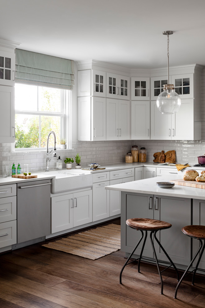 Example of a large farmhouse dark wood floor and brown floor eat-in kitchen design in DC Metro with a farmhouse sink, white cabinets, quartz countertops, white backsplash, subway tile backsplash, stainless steel appliances, an island, white countertops and shaker cabinets
