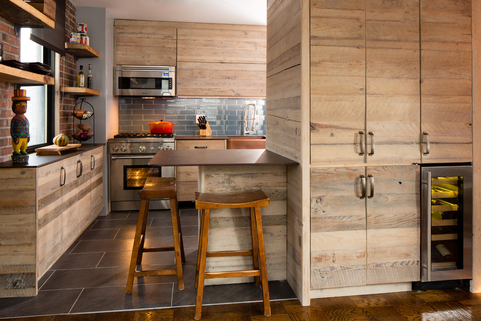 Eat-in kitchen - small transitional u-shaped ceramic tile eat-in kitchen idea in New York with a farmhouse sink, flat-panel cabinets, light wood cabinets, stainless steel appliances, quartz countertops, blue backsplash, glass tile backsplash and a peninsula