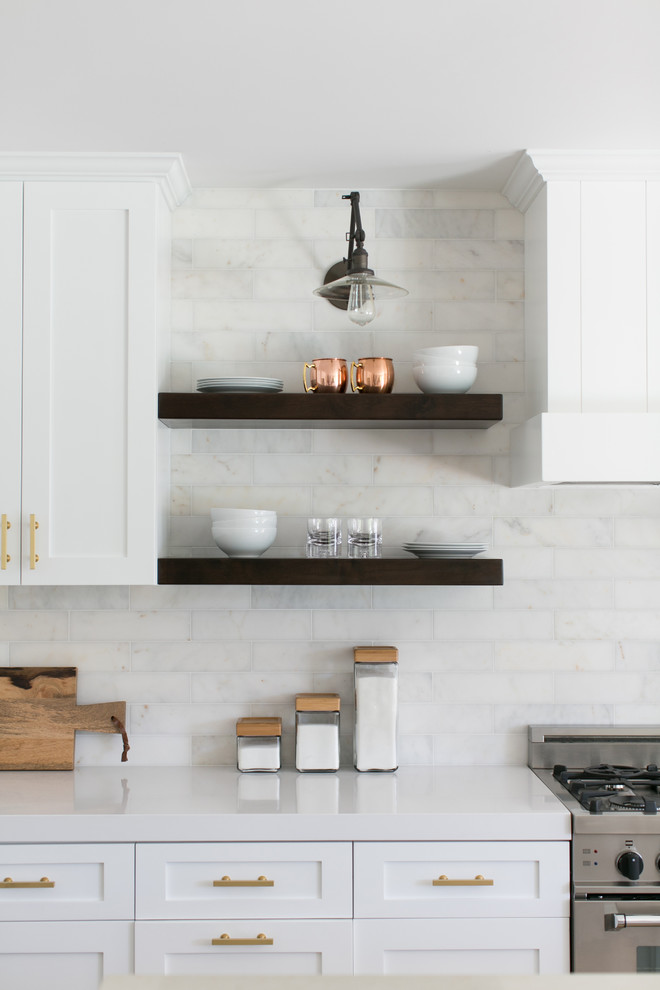 Eat-in kitchen - mid-sized country medium tone wood floor eat-in kitchen idea in Orange County with shaker cabinets, white cabinets, white backsplash, subway tile backsplash, stainless steel appliances and an island