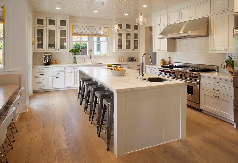 Inspiration for a cottage galley medium tone wood floor eat-in kitchen remodel in San Francisco with an undermount sink, shaker cabinets, white cabinets, white backsplash, subway tile backsplash, stainless steel appliances and an island