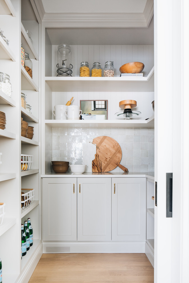 Small transitional u-shaped light wood floor and brown floor kitchen pantry photo in Chicago with shaker cabinets, gray cabinets, gray backsplash, no island, white countertops, quartz countertops and terra-cotta backsplash