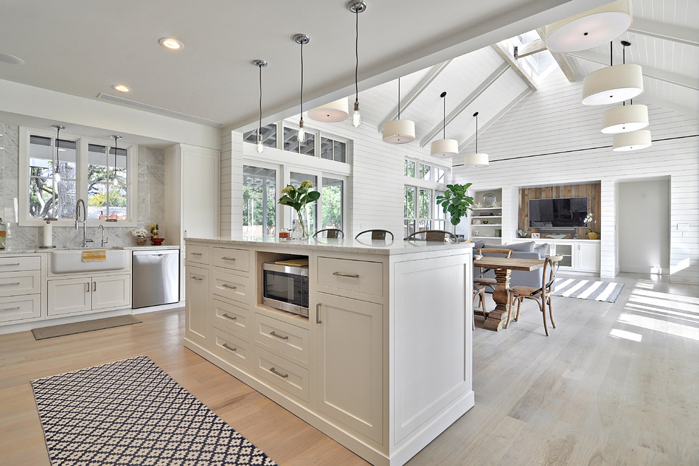 Example of a farmhouse open concept kitchen design in Austin with a farmhouse sink, white cabinets, stainless steel appliances and gray backsplash