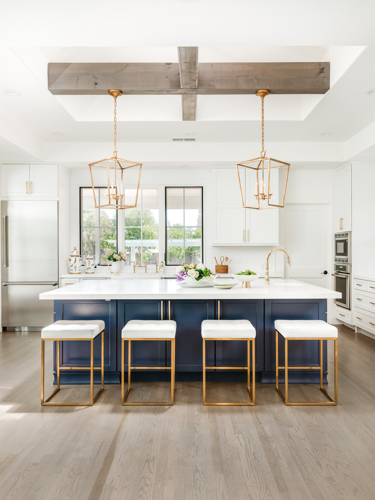 Inspiration for a large cottage u-shaped light wood floor and gray floor eat-in kitchen remodel in San Francisco with shaker cabinets, blue cabinets, white backsplash, an island, white countertops, a farmhouse sink, quartz countertops, ceramic backsplash and stainless steel appliances