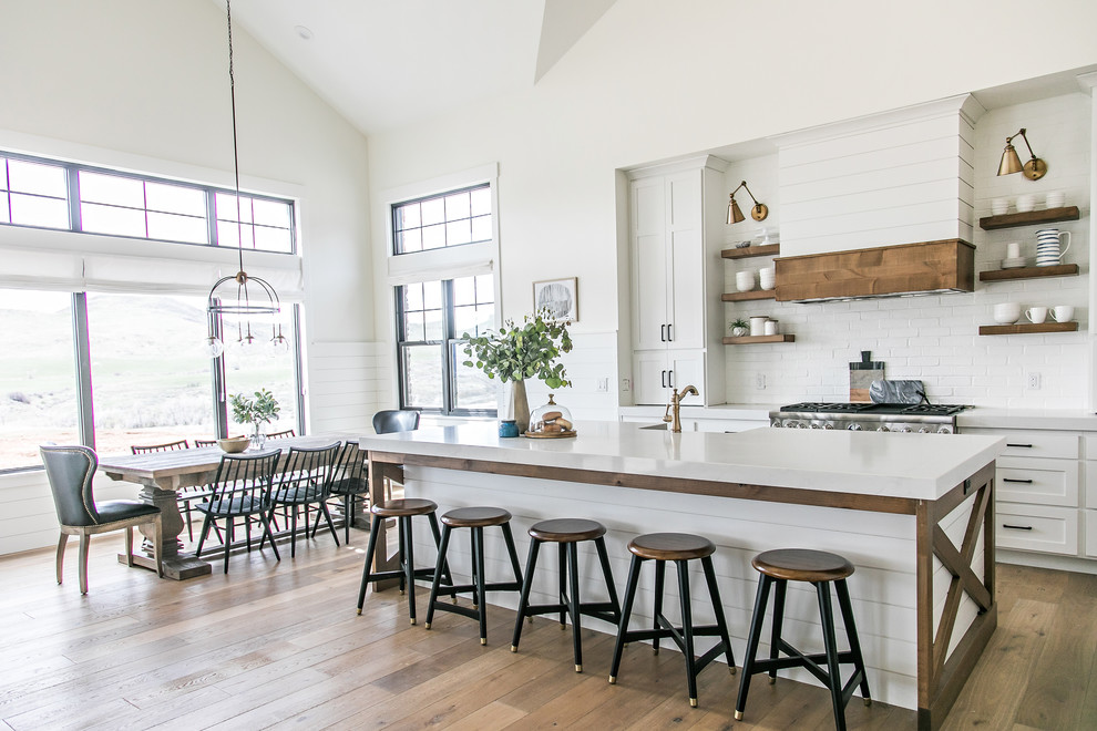 Inspiration for a country light wood floor eat-in kitchen remodel in Salt Lake City with open cabinets, white backsplash, stainless steel appliances and an island