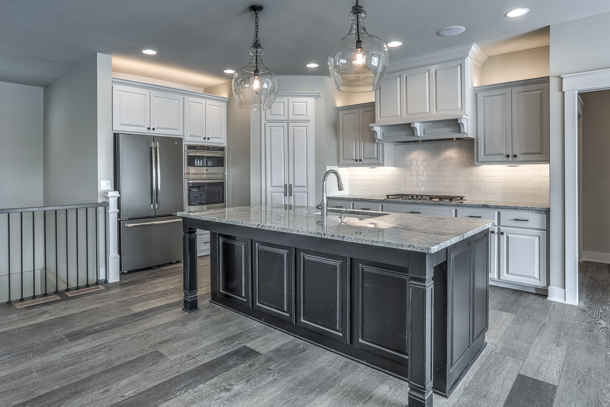 Open concept kitchen - farmhouse l-shaped vinyl floor and gray floor open concept kitchen idea in Omaha with an undermount sink, raised-panel cabinets, white cabinets, granite countertops, white backs
