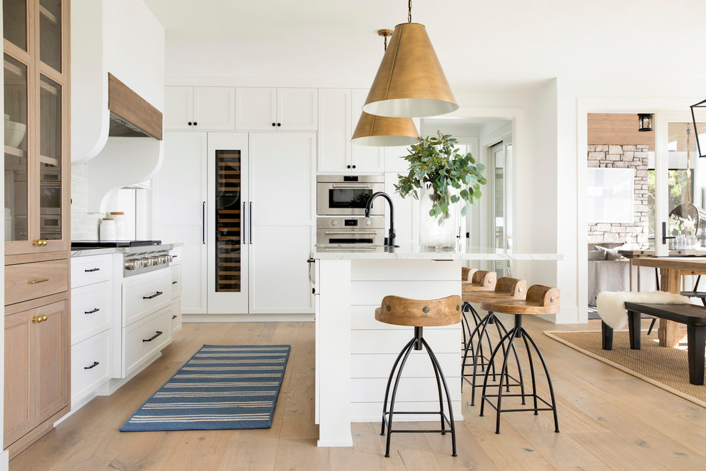 Eat-in kitchen - country light wood floor eat-in kitchen idea in Minneapolis with shaker cabinets, white cabinets, paneled appliances, an island and gray countertops