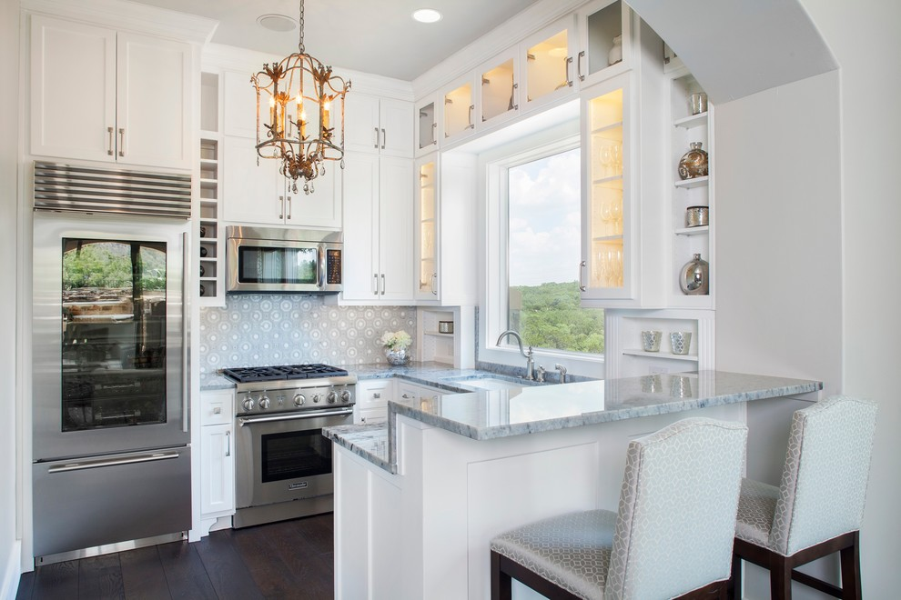 Kitchen - small traditional u-shaped dark wood floor kitchen idea in Austin with an undermount sink, glass-front cabinets, white cabinets, multicolored backsplash, stainless steel appliances and a peninsula