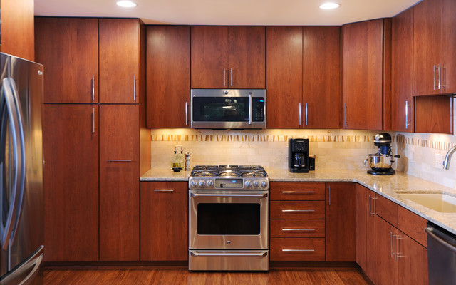 Example of a minimalist u-shaped medium tone wood floor eat-in kitchen design in Nashville with an undermount sink, medium tone wood cabinets, granite countertops, stainless steel appliances and a peninsula