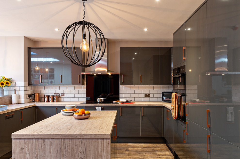 Large trendy u-shaped medium tone wood floor and beige floor open concept kitchen photo in Oxfordshire with an island, flat-panel cabinets, gray cabinets, wood countertops, white backsplash, subway tile backsplash, stainless steel appliances and beige countertops