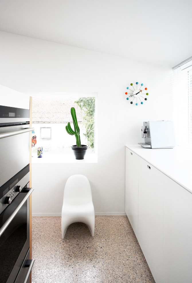 Example of a minimalist kitchen design in Other with stainless steel appliances