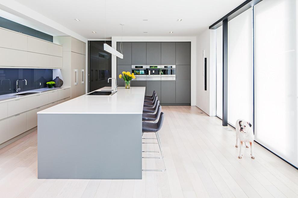 Foto de cocina escandinava con fregadero bajoencimera, armarios con paneles lisos, puertas de armario grises, salpicadero azul, salpicadero de vidrio templado y barras de cocina