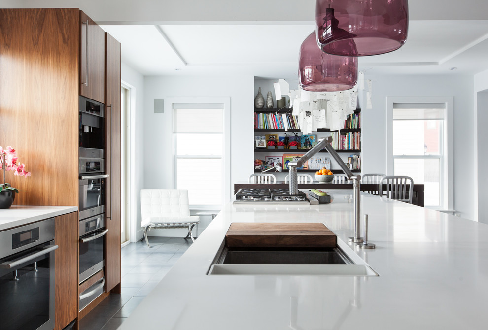 Example of a trendy eat-in kitchen design in Other with flat-panel cabinets, medium tone wood cabinets and stainless steel appliances
