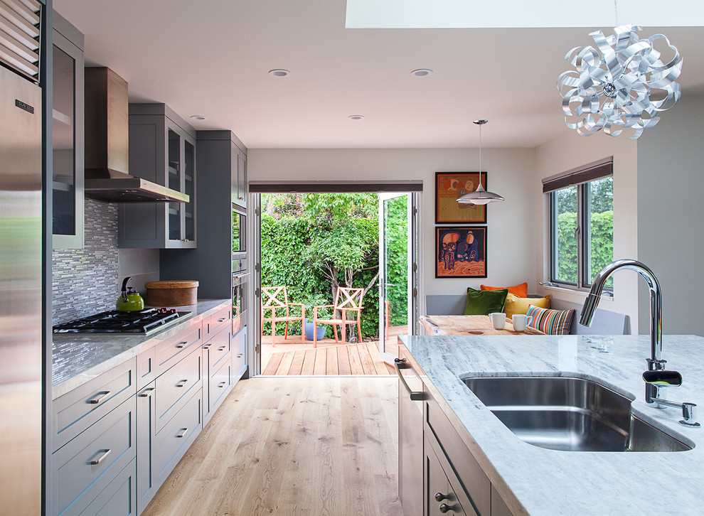 Transitional single-wall medium tone wood floor open concept kitchen photo in San Francisco with an undermount sink, shaker cabinets, blue cabinets, quartzite countertops, multicolored backsplash, porcelain backsplash, stainless steel appliances and an island
