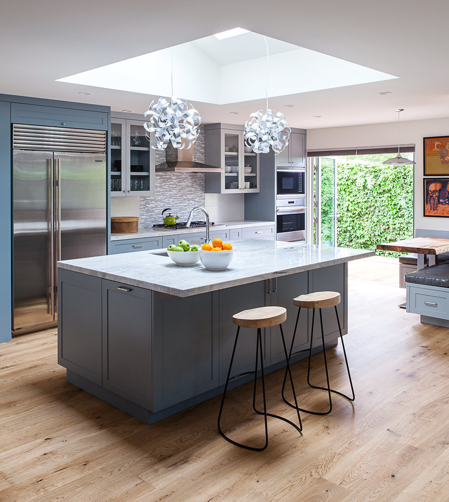 Example of a huge minimalist single-wall medium tone wood floor open concept kitchen design in San Francisco with an undermount sink, shaker cabinets, blue cabinets, quartzite countertops, multicolored backsplash, porcelain backsplash, stainless steel appliances and an island