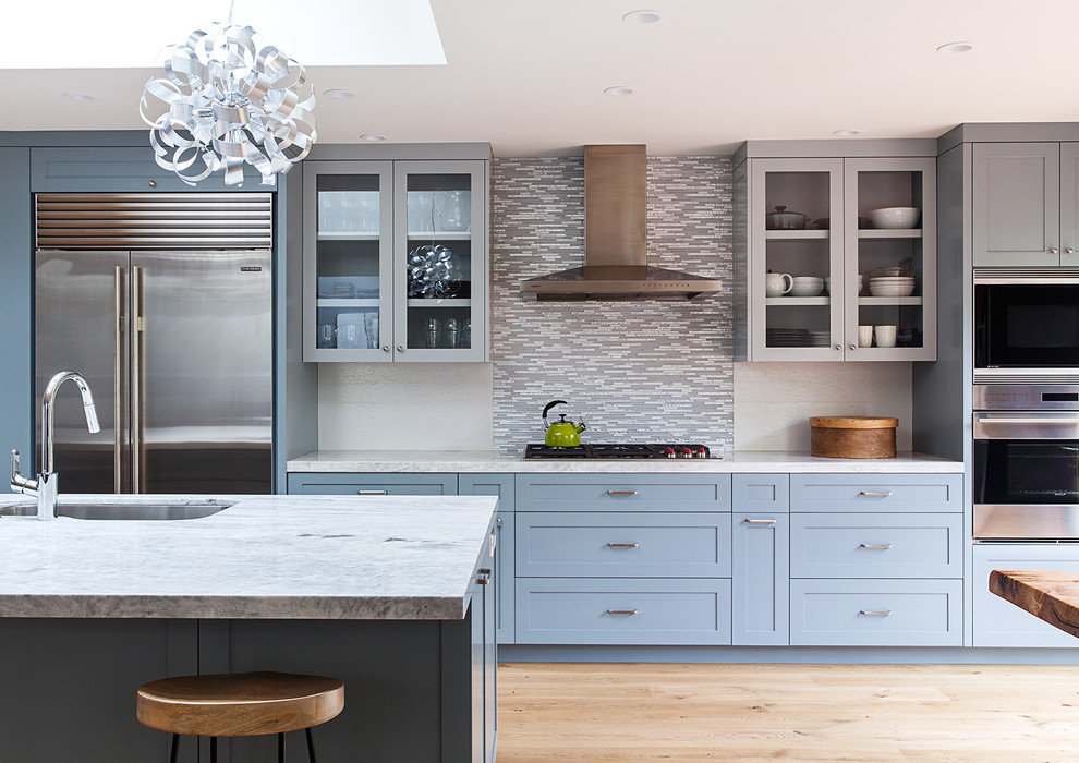 Example of a huge minimalist l-shaped medium tone wood floor open concept kitchen design in San Francisco with an undermount sink, shaker cabinets, blue cabinets, quartzite countertops, multicolored backsplash, porcelain backsplash, stainless steel appliances and an island