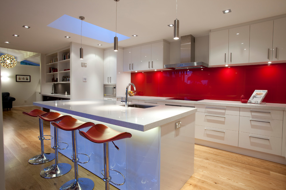 Example of a minimalist kitchen design in Auckland with red backsplash, glass sheet backsplash, an undermount sink, flat-panel cabinets, white cabinets and quartz countertops