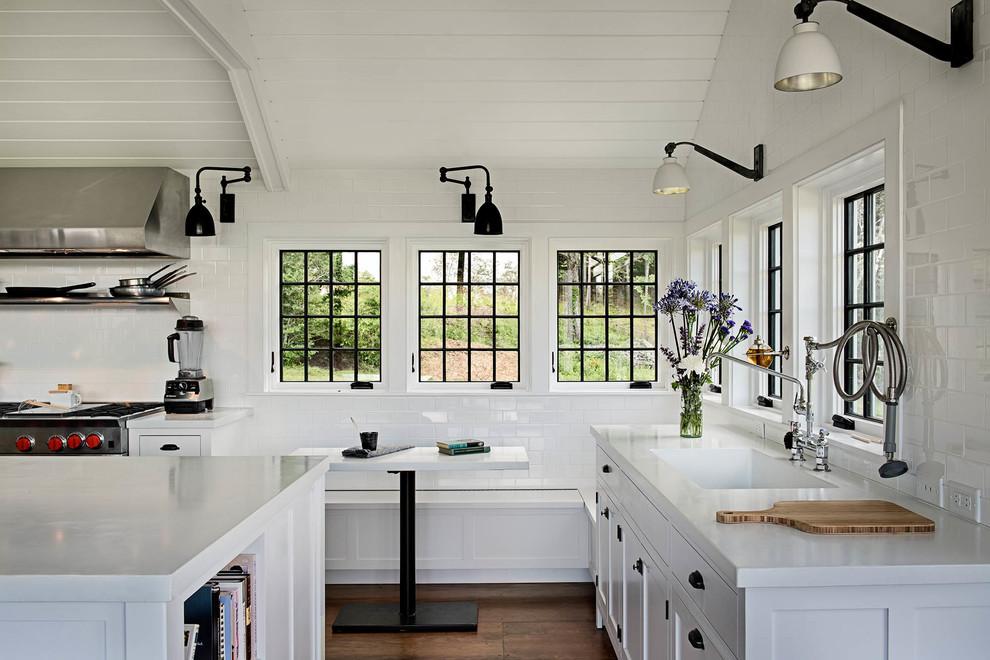 Example of a farmhouse dark wood floor kitchen design in New York with shaker cabinets, white backsplash and subway tile backsplash