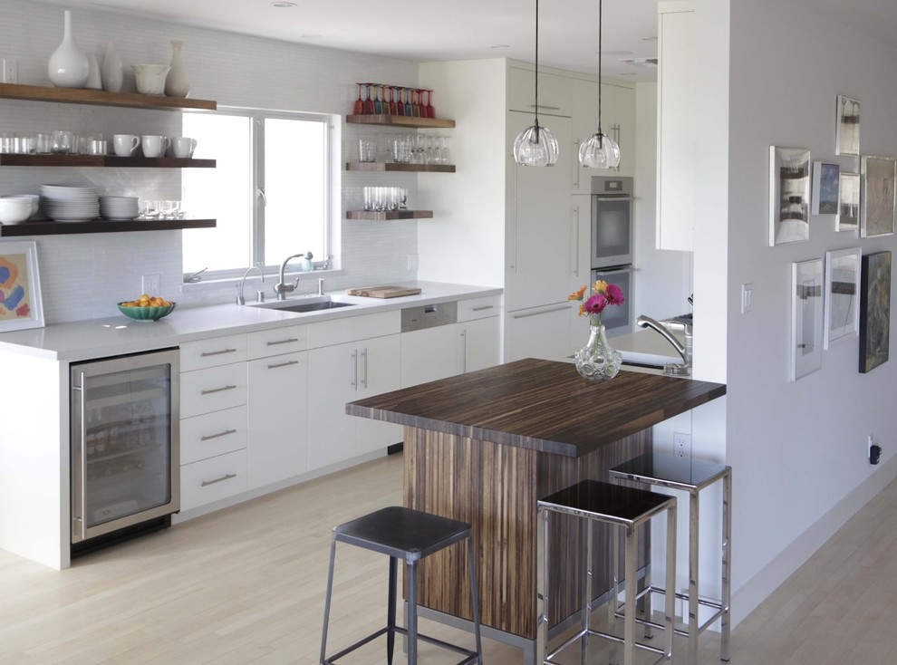 Inspiration for a modern galley kitchen remodel in Birmingham with a single-bowl sink, open cabinets, white cabinets, paneled appliances, quartz countertops and white backsplash